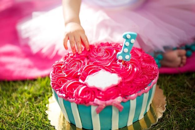 La main de la petite fille goûte un beau gâteau en forme de fleur rose