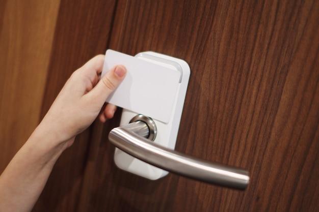 Main de petite fille tenant une carte-clé blanche pour déverrouiller la porte brune.