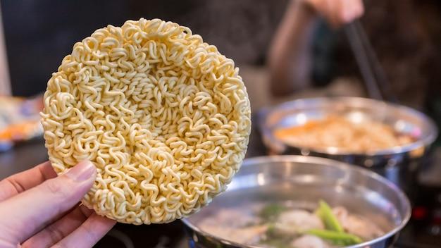 Main pinçant nouille instantanée coréenne ou nouilles sèches en cercle