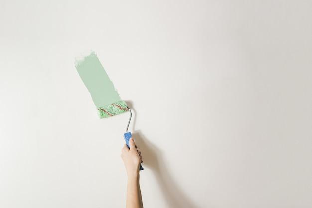 La main avec un pinceau contre le mur blanc. redécorer, rénover la pièce ou l'espace de vie