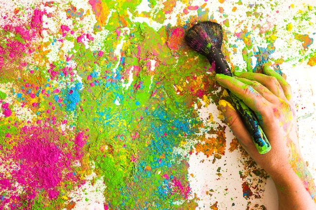 Main avec pinceau sur des couleurs vives et sèches