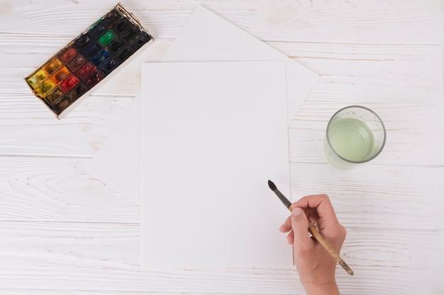 Main avec pinceau près de papier, verre et set d'aquarelles