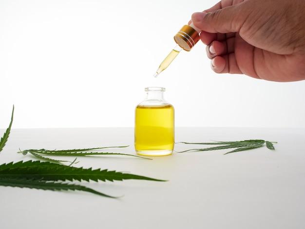 Main Avec Pipettes Et Huile D'extrait De Cannabis. Photo Premium