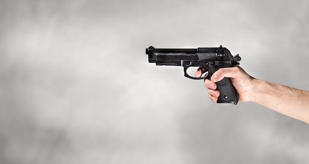 Main avec pistolet en gris