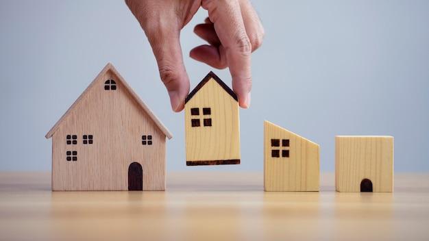 Main de plan rapproché choisissant le modèle de maison et projetant d'acheter la propriété