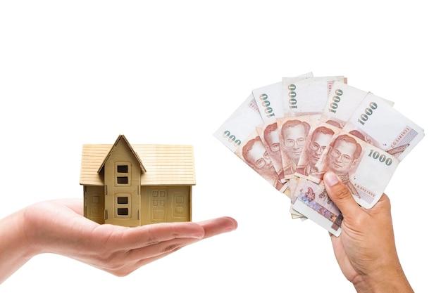 Main de plan rapproché un homme et une femme tenant une banque d'argent et une maison modèle sur le fond blanc. prêts immobiliers pour concept immobilier