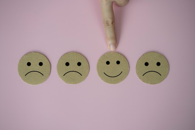 Main de plan rapproché sélectionnez le papier heureux d'icône de visage de sourire de visage coupé sur le fond rose