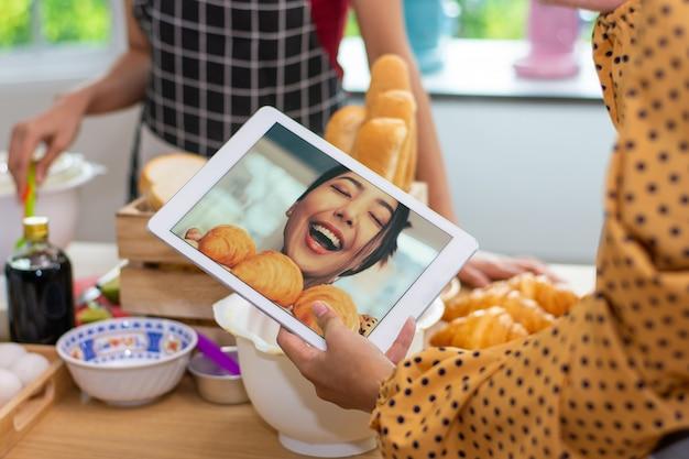 Main de plan rapproché tenant la petite entreprise en ligne de comprimé heureuse avec le croissant dans la boutique de boulangerie