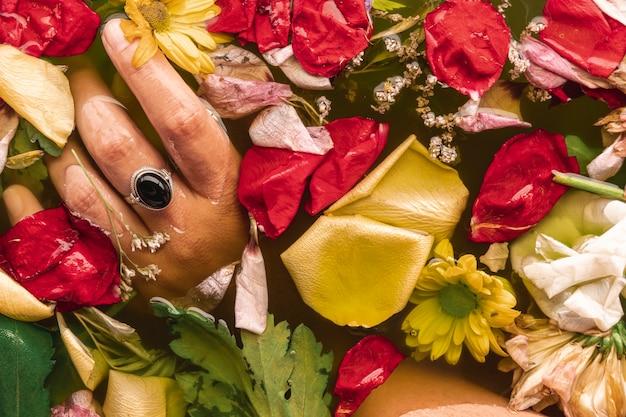 Main plat poser des fleurs dans l'eau noire