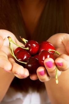 Main pleine de cerises rouges