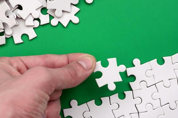 La main plie un puzzle blanc et un tas de pièces de puzzle non peignées se trouve