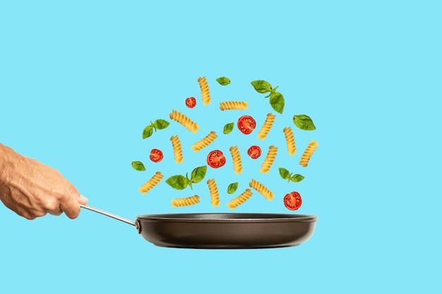 Main avec une poêle à frire et des pâtes italiennes avec des tomates et du basilic sur un fond bleu de couleur c...