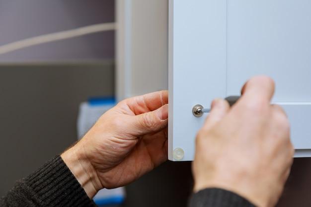 Main sur la poignée d'installation porte dans l'armoire de cuisine avec un tournevis