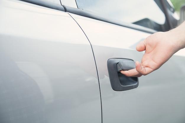 Main sur la poignée. main de l'homme ouvrant une porte de voiture