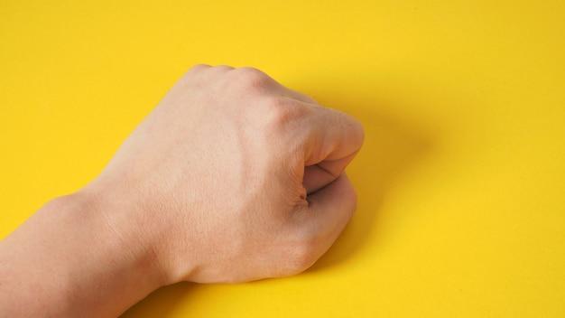 La main de poing est isolée sur fond jaune.