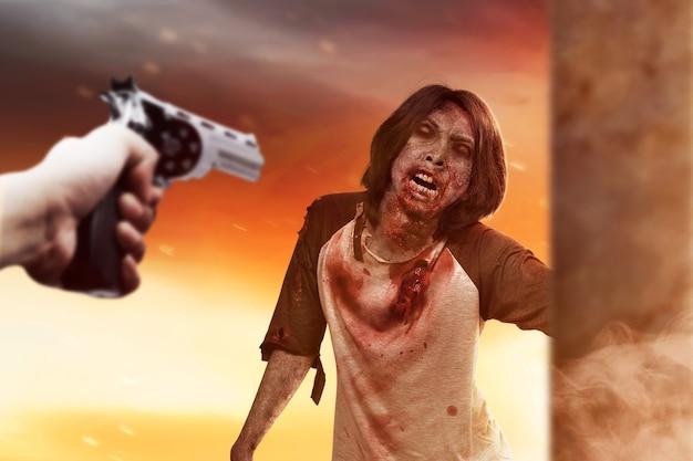 Main pointant une arme sur un zombie. notion d'halloween
