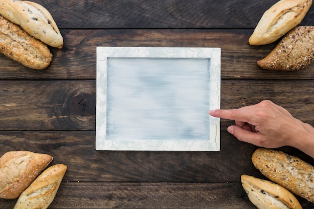 Main pointant au plateau près des pains de pain