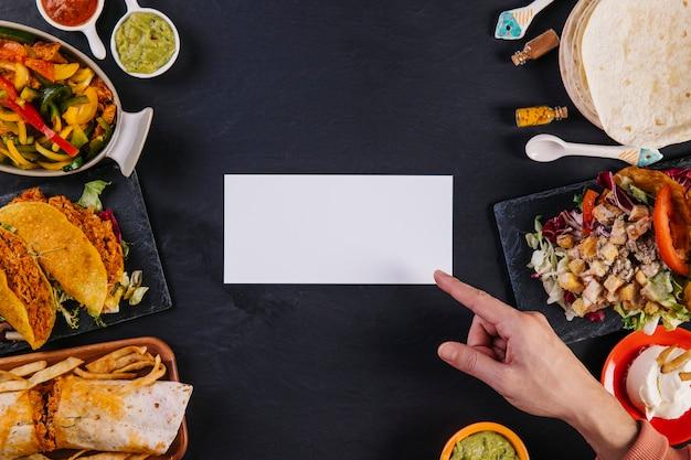 Main pointant sur du papier près de la nourriture mexicaine