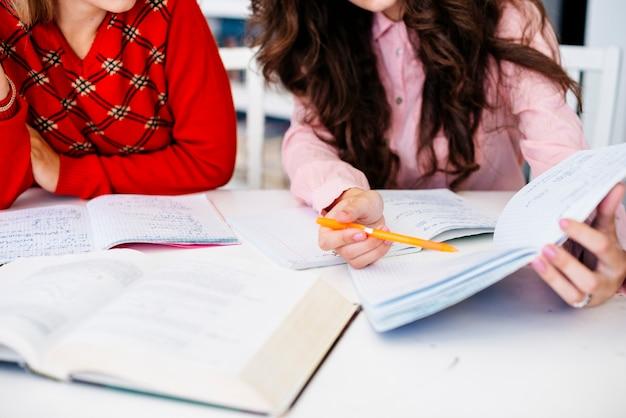 Main, pointant sur des notes dans le cahier