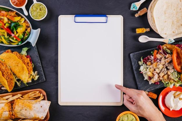 Main, pointant sur presse-papiers parmi la nourriture mexicaine
