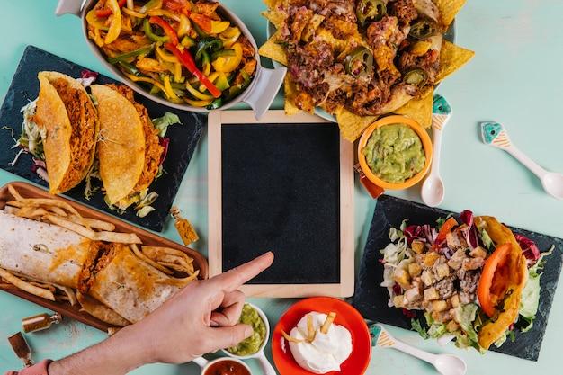 Main, pointant sur tableau noir au milieu des plats mexicains