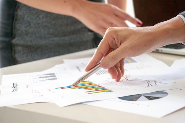 La main pointe les données du rapport sur la table.