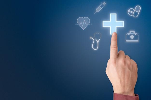 La main pointe vers le signe de la croix médicale. signe de médecine en appuyant sur la main. l'homme appuie sur le signe de croix médicale rougeoyant, l'assurance sur l'écran virtuel. homme d'affaires en appuyant sur l'icône en forme de croix sur fond bleu