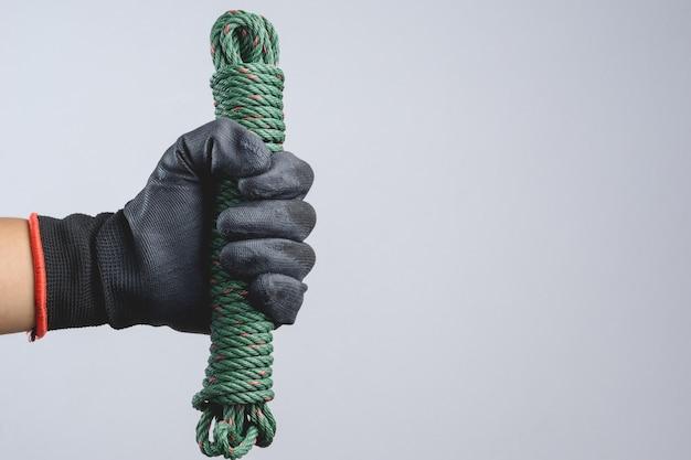 Main portant un gant foncé et tenant un cordon de parachute vert en nylon comme un ravisseur
