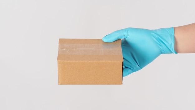 Main portant un gant médical bleu et tenant une boîte brune isolée sur fond blanc.
