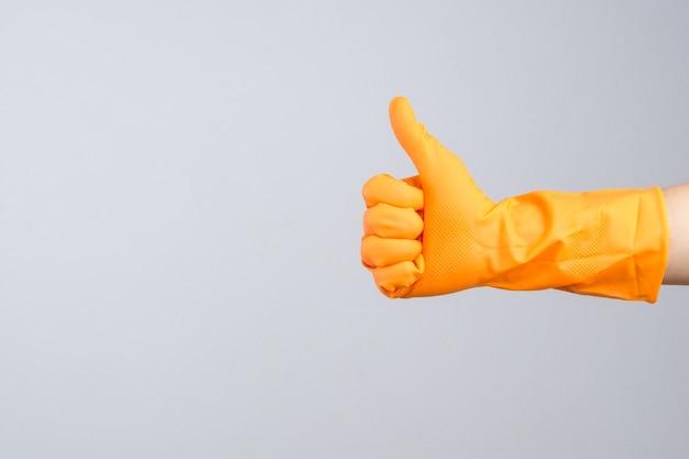 Main portant un gant de protection en caoutchouc avec le pouce levé