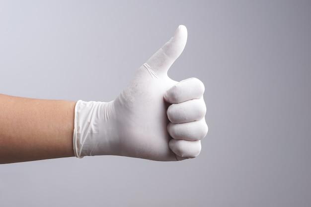 Main, portant des gants en latex avec le pouce vers le haut de geste