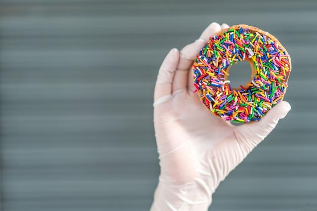 Main portant des gants en latex, tenant un beignet glacé au chocolat frais et regardant le trou du beignet.