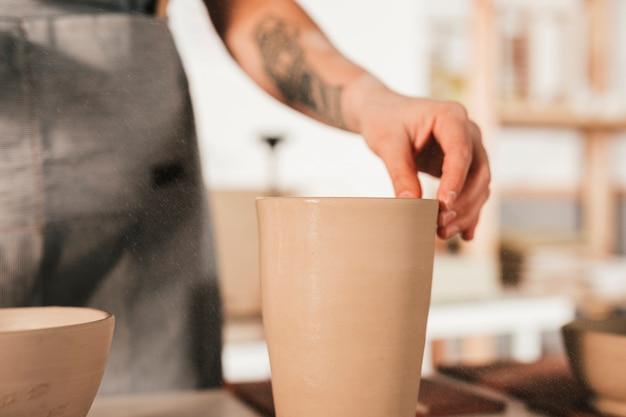 La main de potter tenant le vase en terre cuite