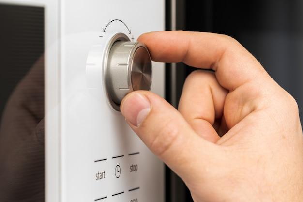 Main poussant le bouton du four à micro-ondes pour la cuisson des aliments dans la cuisine