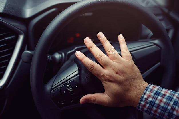 Main poussant le klaxon pendant la conduite