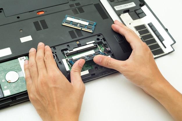 La main poussent la ram change pour l'ordinateur portable, concept d'ordinateur de réparation.