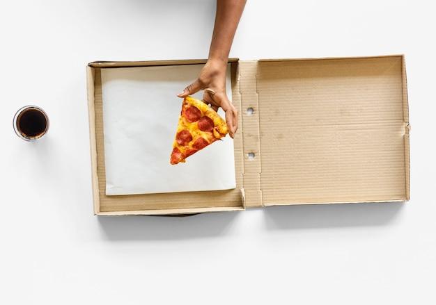 Main prenant la dernière tranche de pizza de la boîte de livraison