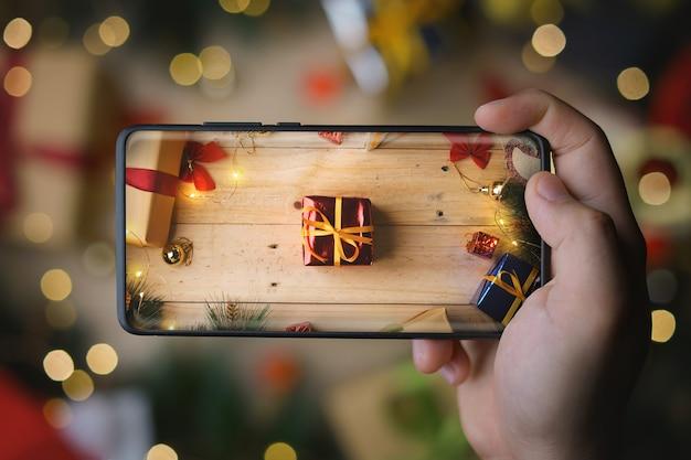 Main prenant une photo de cadeau de noël de feuille rouge avec smartphone d'affichage infini