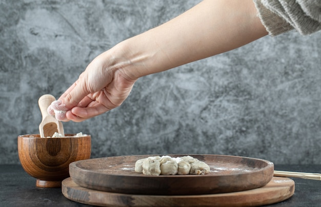 Main en prenant une pincée de farine dans un bol en bois sur fond gris.