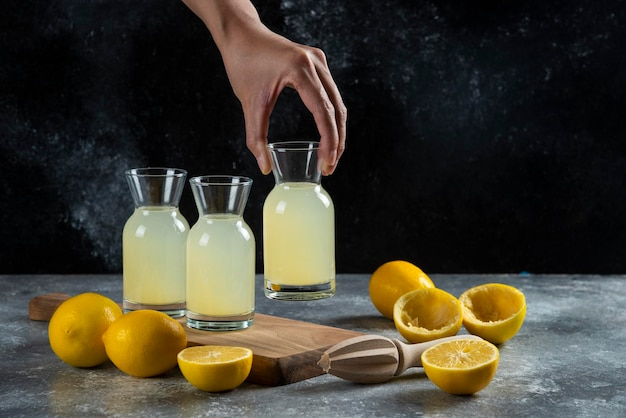 Une main prenant un pot de jus de citron.
