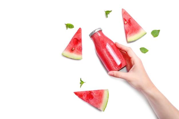 Main prenant un smoothie frais et savoureux à la pastèque dans une bouteille en verre isolée sur fond blanc. vue de dessus. espace de copie.
