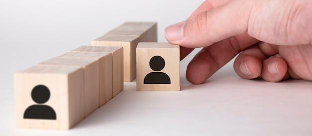 Main prendre un cube en bois avec l'icône de l'homme. notion de direction