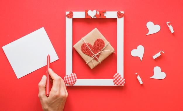 Main près du papier, cadre avec titre de l'amour, symboles du présent et du coeur