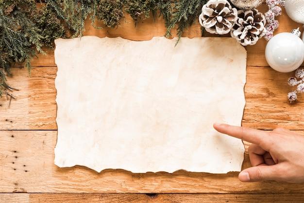 Main près du papier entre les décorations de noël