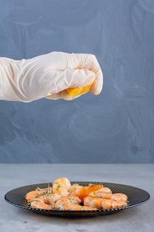 Main pressant le citron dans une assiette de délicieuses crevettes sur une surface en pierre
