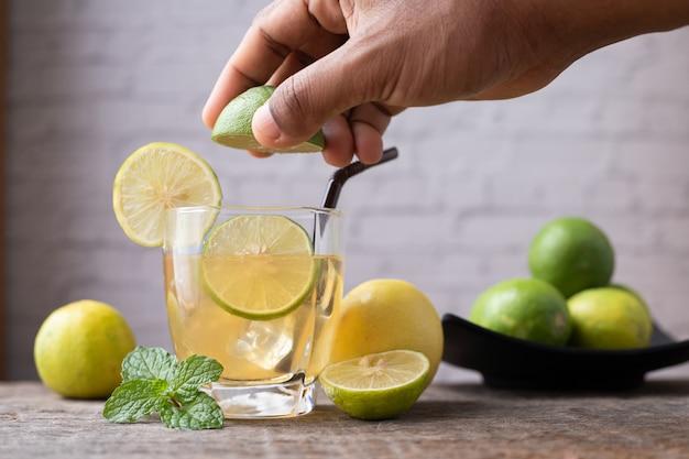 Main pressant le jus de citron et le citron en tranches, concept de soins en bonne santé.