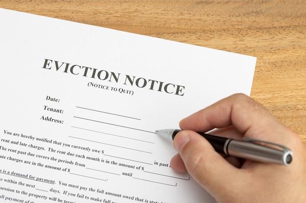 Main prête à remplir un document d'avis d'expulsion