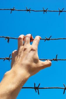 Main de prison et ciel.