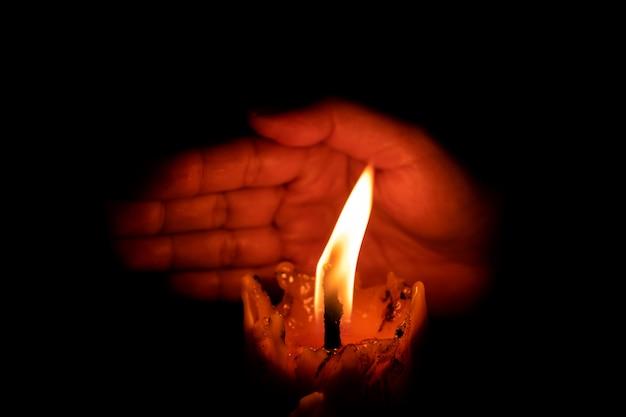 Main protégeant la lumière des bougies du vent dans l'obscurité sur fond noir