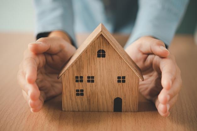 Main protégeant la maison des icônes - le concept d'assurance.